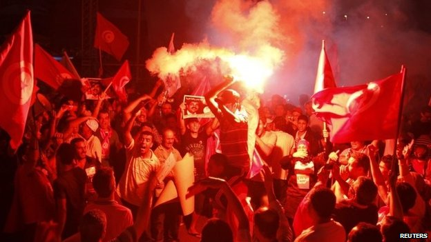 Anti-government protesters hold flares and shout slogans during a demonstration in Tunis August 24, 2013.