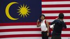 A tourist poses for a picture in front of a national flag ahead of Malaysia's 56th Independence Day celebrations in downtown Kuala Lumpur on 20 August 2013