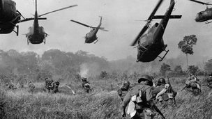 Hovering US Army helicopters pour machine gun fire into the tree line to cover the advance of ground troops