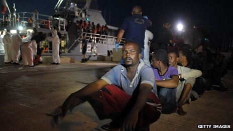Migrants wait to board a bus after disembarking from a Maltese patrol vessel at Hay Wharf in Valletta, after being rescued on 10 July 2013