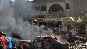 A burning car is seen at the entrance of a mosque which was attacked by a car bomb, in the northern city of Tripoli, Lebanon