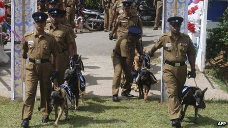 Sri Lankan policemen walk with sniffer dogs at the ceremony in Kandy on Monday