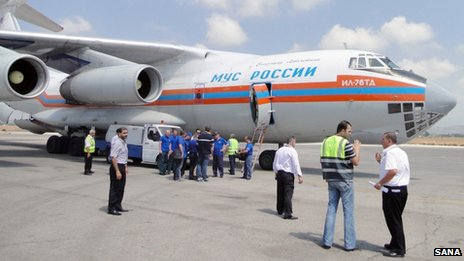 A handout picture released by the official Syrian Arab News Agency (SANA) on August 27, 2013, allegedly shows people gathering near a Russian aircraft loaded with humanitarian aid, food and medical supplies after its arrival at Latakia airport in Syria.