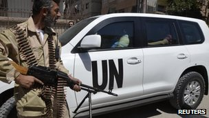 "A Free Syrian Army fighter carries his weapon as he and fellow fighters escort a convoy of U.N. vehicles carrying a team of United Nations chemical weapons experts at one of the sites of an alleged chemical weapons attack in Damascus"" suburbs of Zamalka August 28, 2013"
