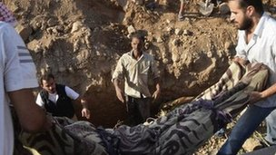 The body of a victim of a suspected chemical weapons attack is lowered into a grave in Hamoria, Damascus (21 August 2013)