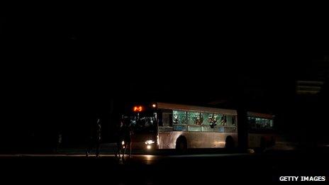 Cubans walk along a dark Havana street, lit only by bus headlights