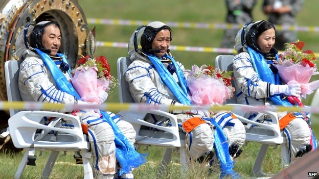 Chinese astronaut (L-R) Zhang Xiaoguang, Nie Haisheng and Wang Yaping sit on their chairs after getting out of the Shenzhou-10 spacecraft that landed on the grasslands of north China's Inner Mongolia region on 26 June, 2013, after a 15-day mission in space.