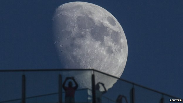 Visitors stand on the roof of a skyscraper as the moon rises over the skyline of Lujiazui financial district of Pudong in Shanghai 16 August, 2013