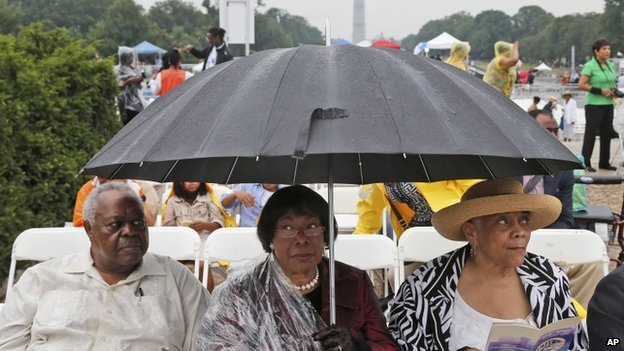 Three people wait under an umbrella in front of the Lincoln Memorial, Washington DC on 28 August 2013