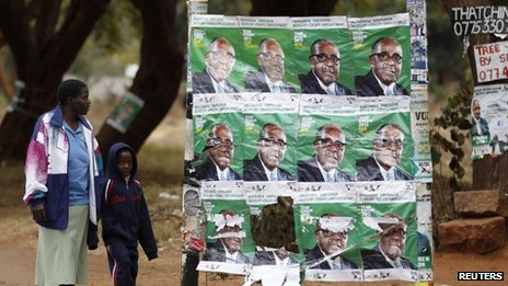 A woman and a child walk past election posters of Zimbabwe's President Robert Mugabe in Harare on 30 July 2013