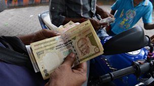 An Indian petrol pump employee counts Indian currency in Siliguri on 28 August 2013