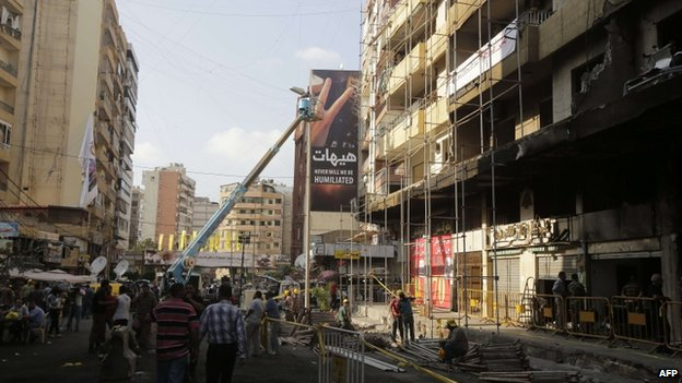 Workers from Jihad al-Binaa, a construction company affiliated with the Shia Muslim Hezbollah movement, clear up the neighbourhood where a car bomb exploded the previous week in a southern Beirut stronghold of the pro-Syria group on 19 August, 2013