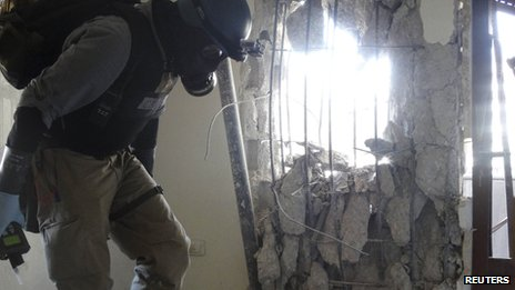 "A U.N. chemical weapons expert, wearing a gas mask, inspects one of the sites of an alleged chemical weapons attack in the Damascus"" suburb of Zamalka August 29, 2013."