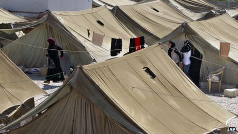 Syrian refugees stand outside their tents at a temporary refugee camp in the eastern Lebanese town of Marj near the border with Syria on 28 August 2013