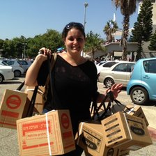 Woman with boxes of gas masks collected from Tel Aviv distribution centre ion 29 August 2013