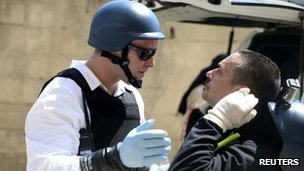 A UN chemical weapons expert checks a colleague after they ended their visit to the site of an alleged chemical weapons attack in the Ain Tarma neighbourhood of Damascus, 29 August