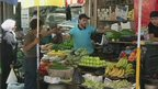 BBC still taken from Bowen package showing people shopping at a fruit stall in Damascus