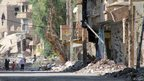 Syrians walk in a heavily damaged street in Syria's eastern town of Deir Ezzor on 26 August, 2013