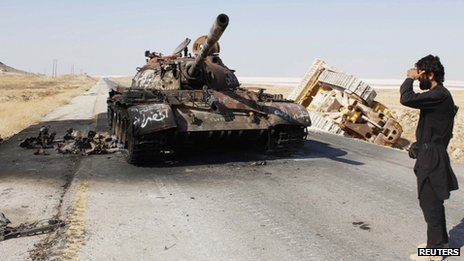 free syrian army fighter and burnt out tank