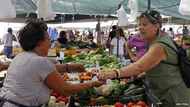 A woman receives a bag of fruits at the Malveira village market on the outskirts of Lisbon August 29, 2013.