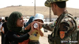 A member of the Kurdish Peshmerga battalions helps a boy drink from a bottle at the Quru Gusik refugee camp in the autonomous Kurdish region of northern Iraq, on August 29, 2013