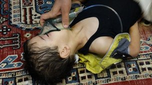 A boy, affected by what activists say is nerve gas, breathes through an oxygen mask in the Damascus suburb of Saqba, August 21, 2013 in this handout provided by Shaam News Network