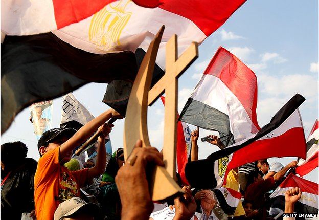 Egyptians hold up sign of cross and crescent - symbolising Christians and Muslims