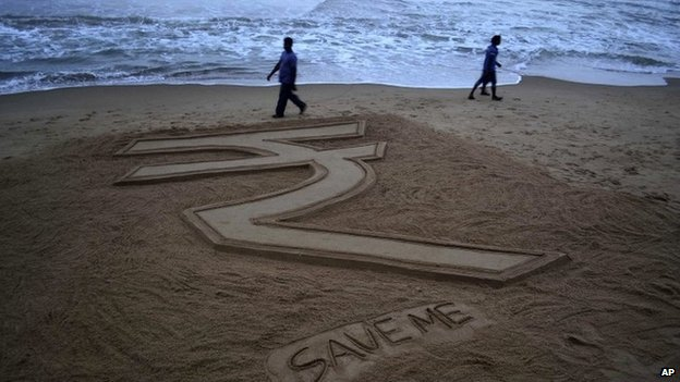 Visitors walk past a sand sculpture depicting the Indian Rupee by  sand artist Sudarshan Pattnaik on the Bay of Bengal coast at Puri, Orissa state, India, Tuesday, Aug.27, 2013.