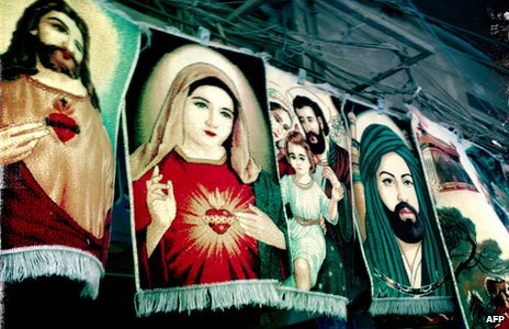 Rugs for sale depicting Christian and Muslim figures in a market in  Baghdad