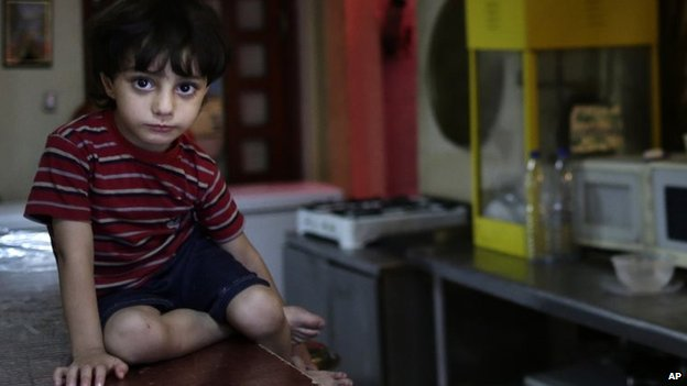 In this Sunday, 25 August, 2013 photo, a Syrian child watches as his mother who fled her home because of Syria's civil war prepares a meal in the kitchen at the Kertaj Hotel in Damascus, Syria.