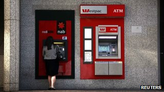 A Westpac automated teller machine (ATM) can be seen next to a woman as she uses a National Australia Bank ATM in central Sydney