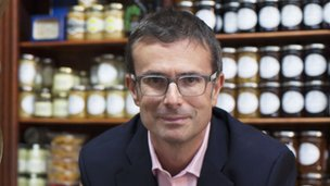 Robert Peston standing in front of stacked jam jars