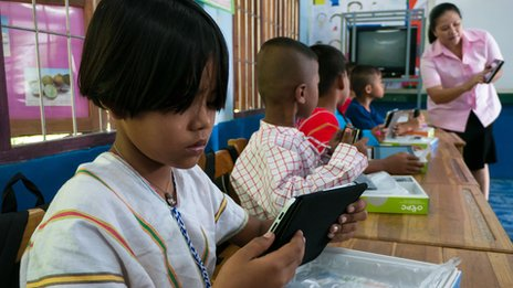 Karen girl using tablet computer in classroom in Thailand