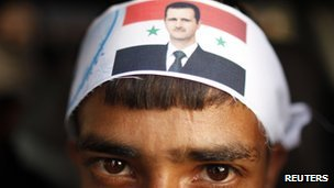 A protester loyal to the Shia Muslim Al-Houthi group, also known as Ansarullah, wears a headband with a picture of Syria's President Bashar al-Assad as he rides a car following a demonstration against potential strikes on the Syrian government, in Sanaa August 30
