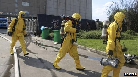 Rescuers in chemical protection suits