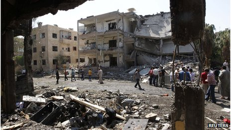 People inspect the damage at a site hit by what activists say was a car bomb in Raqqa province, eastern Syria August 29, 2013