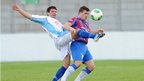 Ballymena's Mark McCullagh attempts to dispossess Neil Dougan of Ards at Dixon Park