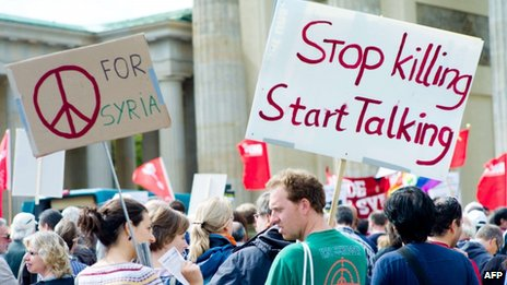 """Protesters against arms exports and a military strike against Syria hold placards reading """"for Syria"""" and """"Stop killing, start talking"""" in front of the Brandenburg Gate in Berlin, Germany on 1 September 2013"""