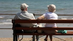 An elderly couple sitting on a bench and looking out to the sea