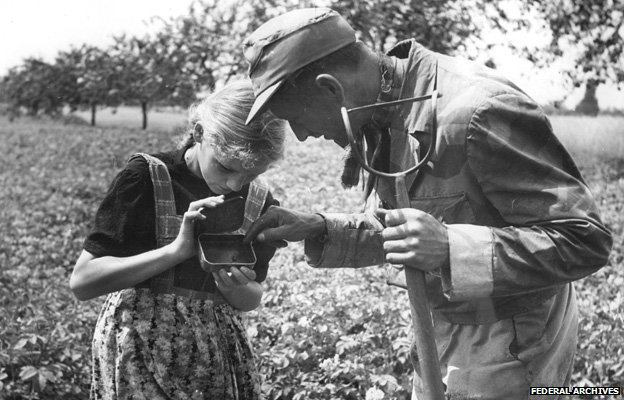 A girl and a man in a field looking at some potato beetles - image taken in East Germany in 1950 (Federal Archives/Bundesarchiv, Bild 183-S99732 / photo: Schmidtke)