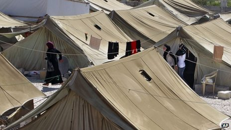 Syrian refugees stand outside their tents, at a temporary refugee camp in the eastern Lebanese town of Marj near the border with Syria, 28 August 2013