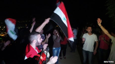Pro-Assad demonstrators wave flags and shout slogans in support of Syrian President Bashar Al-Assad and against a possible US strike at Mount Qasioun, Damascus on 1 September  2013.
