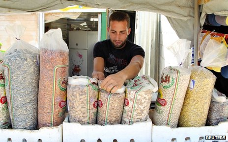 A Syrian refugee displays his goods for sale at Al-Zaatri refugee camp