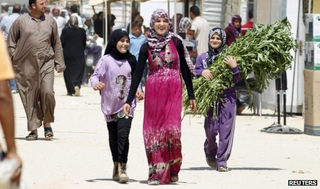Syrian refugees walk on the main market street at Al-Zaatri refugee camp