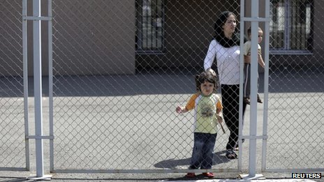 Hevin Youseff, a 28-year-old Syrian woman, walks with her children behind a fence at a detention centre