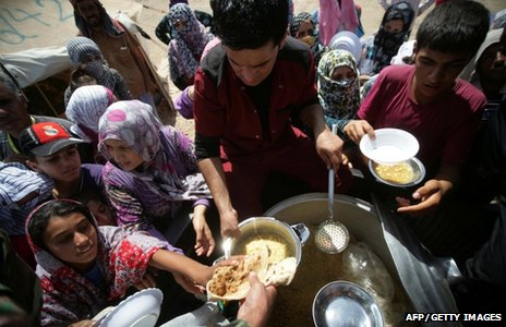 Syrian-Kurdish refugee families queue to get food