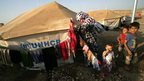 A Syrian-Kurdish refugee woman hangs out her laundry on a clothesline outside a tent provided by the UNHCR at the Quru Gusik refugee camp, east of Arbil
