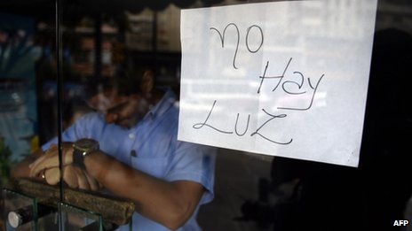 "An employee of a business closed during a blackout stands behind the door with a notice reading ""There's No Electricity"", in Caracas on 3 September, 2013"