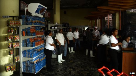 Employees of a supermarket closed due to a blackout, wait for power to be re-established, in Caracas on 3 September, 2013.
