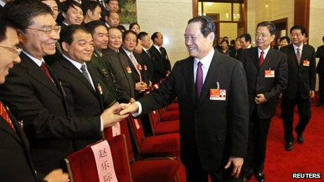 Chinese former Politburo Standing Committee member, Zhou Yongkang, centre, shakes hands with delegates at the National People's Congress at the Great Hall of the People in Beijing, in this picture taken 12 March 2011